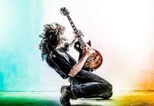 Guitarrista tocando ajoelhado no palco.
